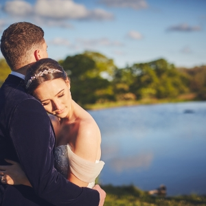 Brides cuddles in a leans her head on her grooms shoulder by the lake at Upton Barn
