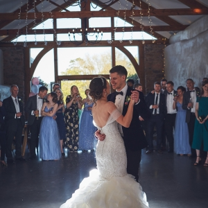 Bride and Groom smile as they take thier first dance in front of guests in the Cider Barn