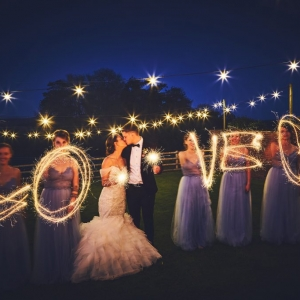 "Bridesmaids surround the Bride and Groom and spell out the word ""LOVE"" with sparklers at night under the festoon lights"
