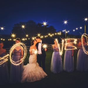 """Bridesmaids surround the Bride and Groom and spell out the word """"LOVE"""" with sparklers at night under the festoon lights"""