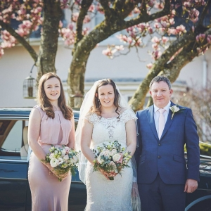 Bride, her father and bridesmaid pose in front of the wedding car under the Magnolia tree