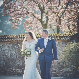 Bride and her father walk into the Walled Garden overlooked by the Magnolia tree