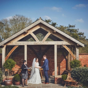 Bride and Groom exchange vows in the Arbour in the Walled Garde