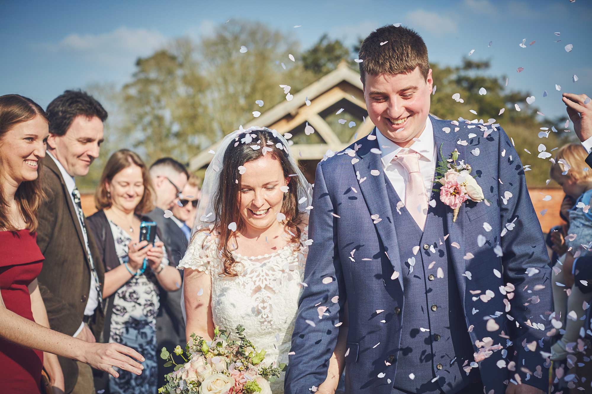 Bride and groom surrounded in a storm of paper confetti in front of the Arbour