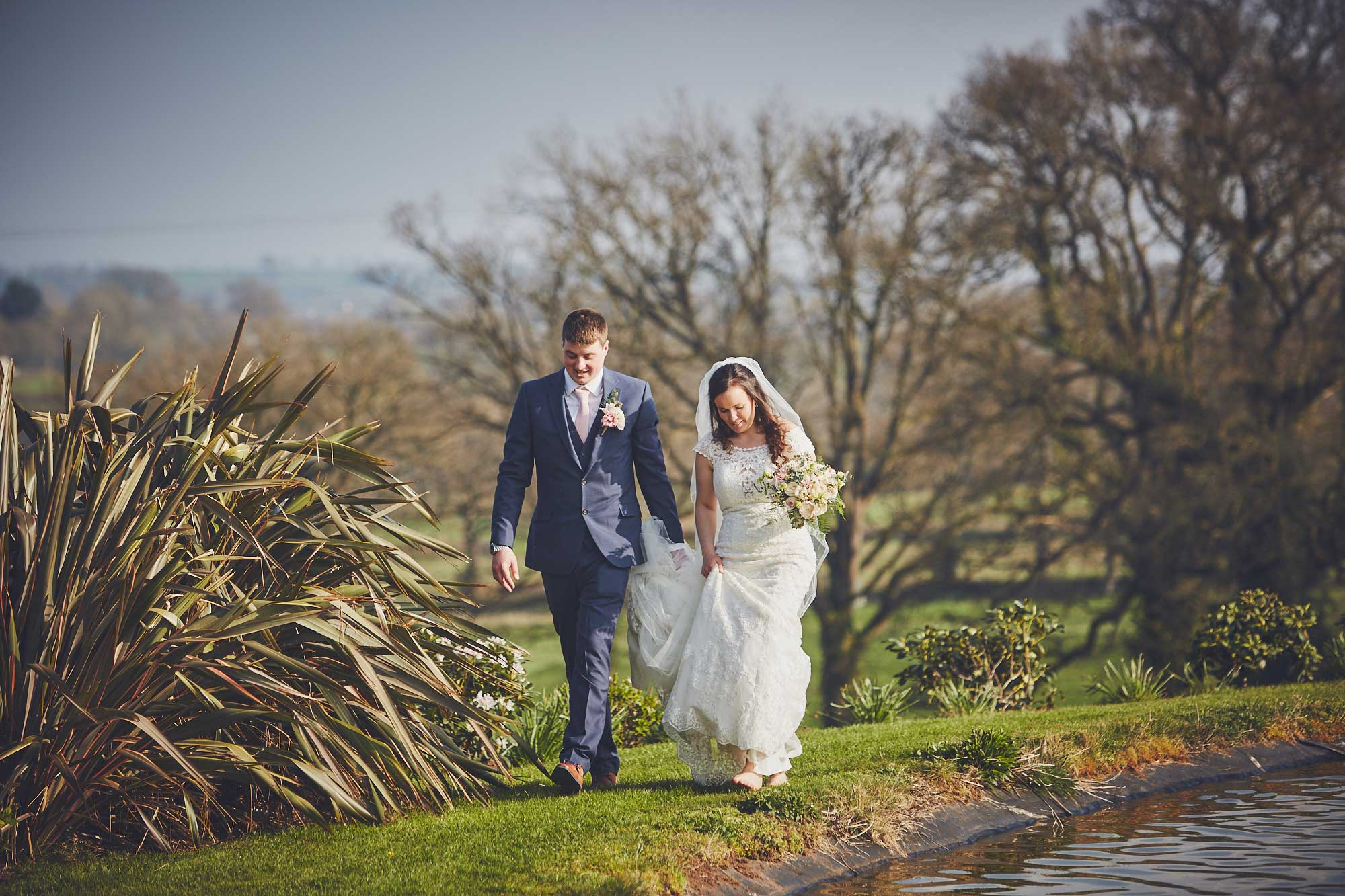 Groom walks holding brides dress off the grass around the lake at Upton barn