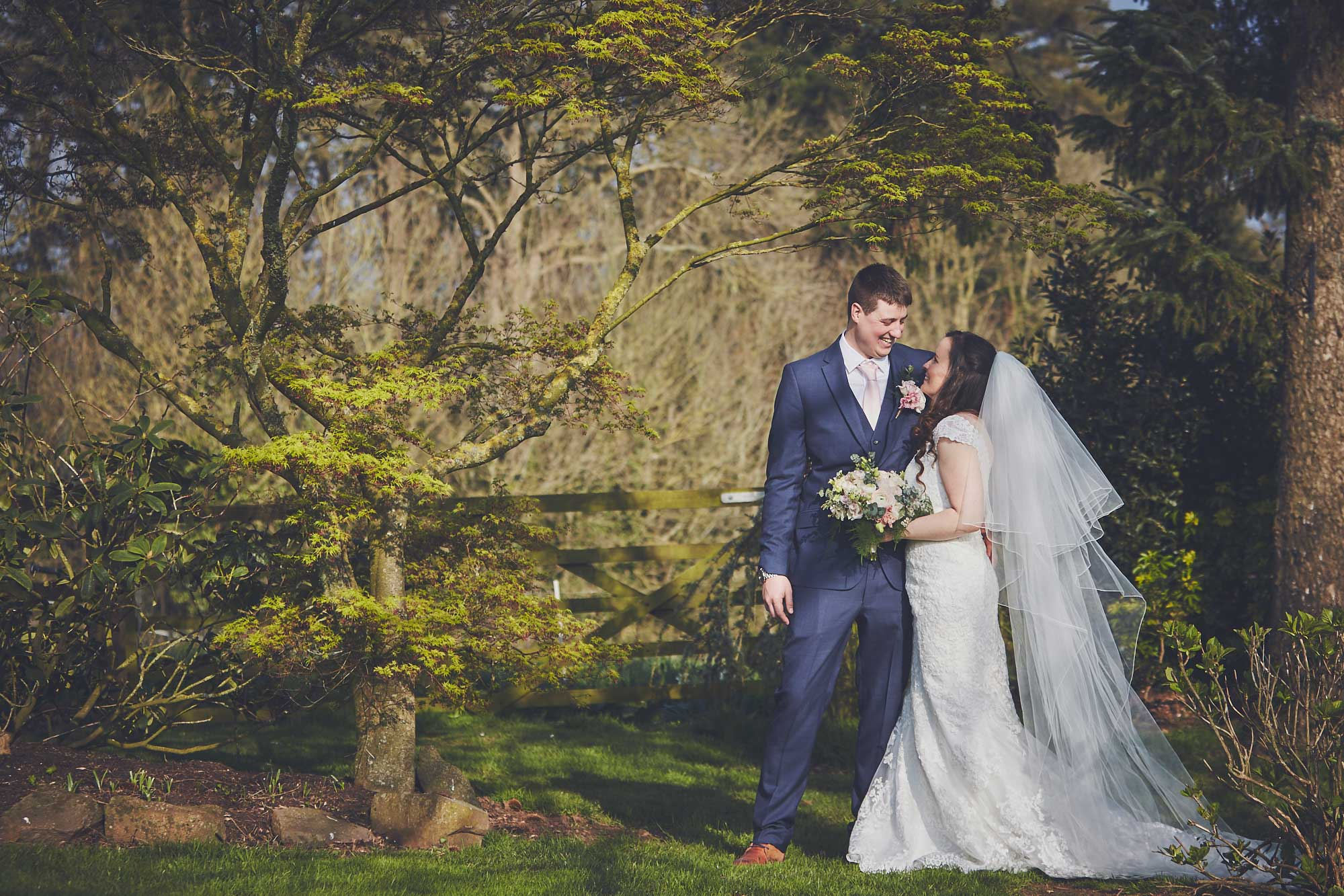 Bride and Groom smile and embrace under trees infront of wooden gate at Upton Barn Wedding venue