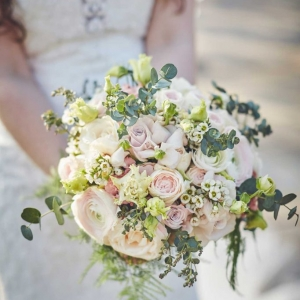 Close up of bridal bouquet of pale pinks and ivory flowers