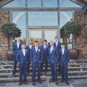 Groomsmen stand in a group on the steps to The Cider Barn at Upton Barn