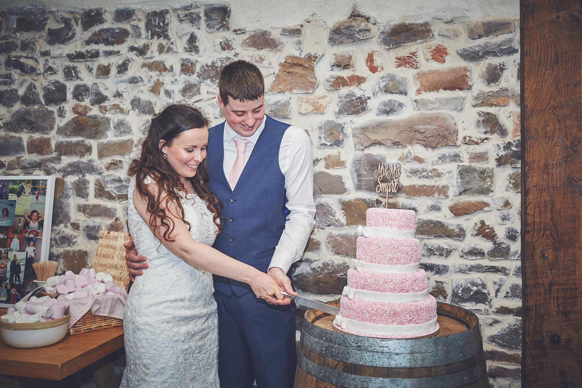 Bride and Groom cut four tier hundreds and thousands wedding cake in The Press Bar at Upton Barn