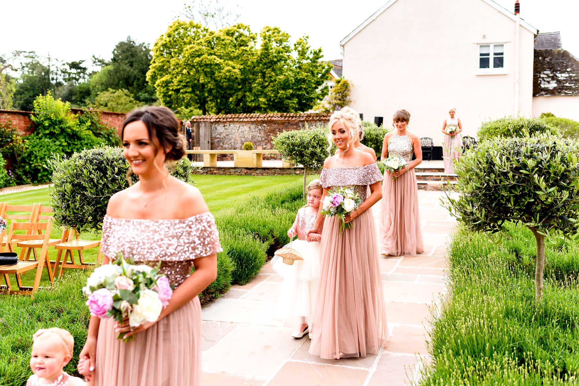 Bridesmaids and flowers girls walk down the aisle of Upton Barns Walled Garden