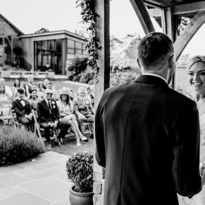 Bride gives broad grin to Groom during vows in Arbour at Upton Barn