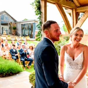 Bride and Groom smile holding hands while exchanging vows in the arbour at Upton Barn watched by guests