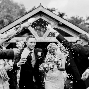 Bride and Groom showered in confetti walking from the Arbour at Upton Barn