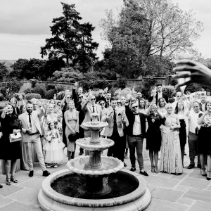 Guests raise glasses to toast happy couple in the walled Garden at Upton Barn