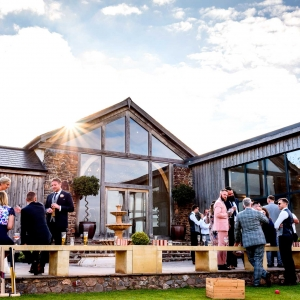 Guests enjoy drinks in the Walled Garden in front of the Cider Barn and Press Bar