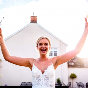 Bride holds two drinks aloft smiling in full sun in the Walled Garden at Upton Barn