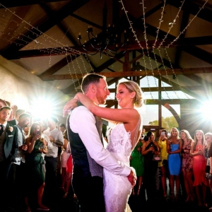 Bride and Groom smile and look into each others eyes while performing their first dance in front of guests in the Cider Barn at Upton Barn