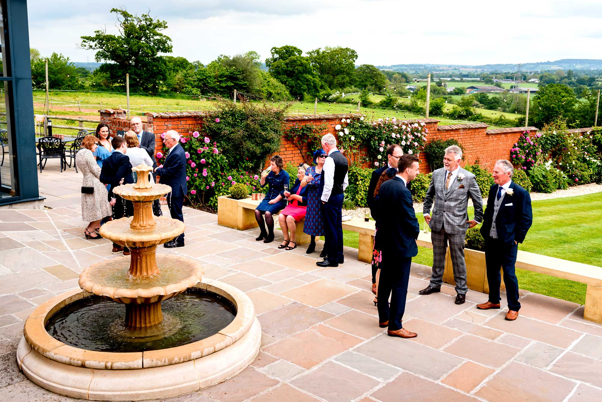 Guests mingle in the Walled Garden at Upton Barn on the patio by the fountain