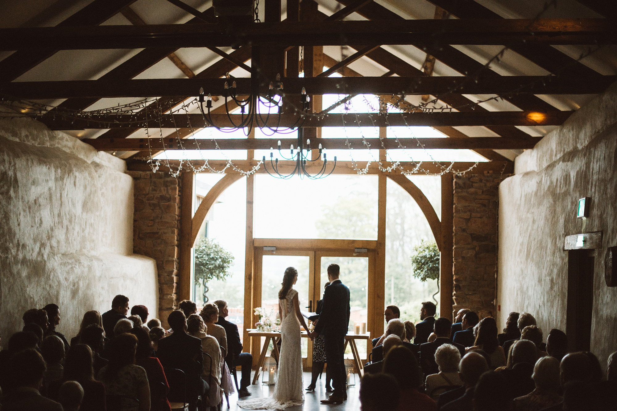 Bride and Groom exchange vows in front of the Cider Barn Windows