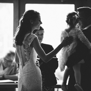 Bride with Groom holding flower girl during wedding ceremony