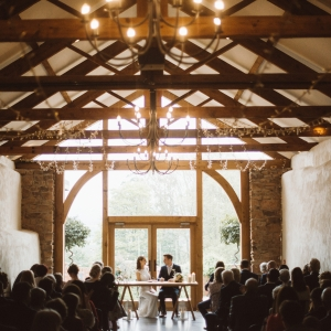 Bride and Groom sign the registrar in the presence of guests in the Cider Barn at Upton Barn