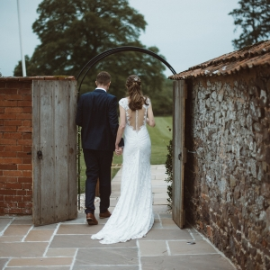 Bride and Groom show thier backs as they exit the Walled Garden