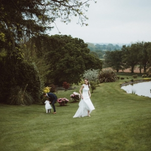 Groom chases after flower girl as bride walks alongside the lake at Upton Barn