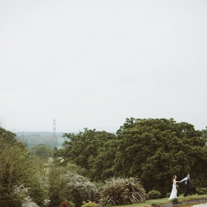 Grooms leads the Bride by her hand around the edge of the lake with the countryside view in the distance