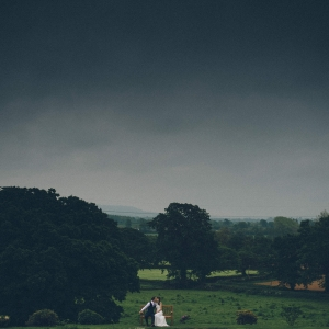 Groom kisses Bride while seated on the bench with large countryside vista engulfing them
