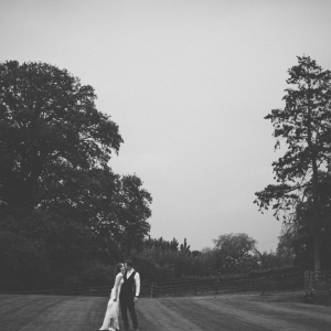 Bride and Groom kiss on the games lawn at Upton Barn and Walled Garden