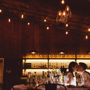 Groom kisses Brides cheek in The Stable Barn at night surrounded by soft lights