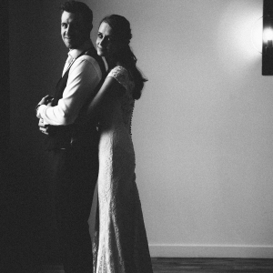 Bride cuddles Groom from behind besides stylish light and plain wall in the Stable Barn at Upton Barn and Walled Garden