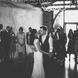 Bride and Groom hold hands as they perform their first dance infront of guests in the Cider Barn