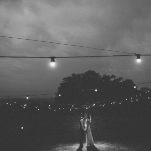 Bride and Groom stand undr festoon lights in the rain at night at Upton Barn wedding venue