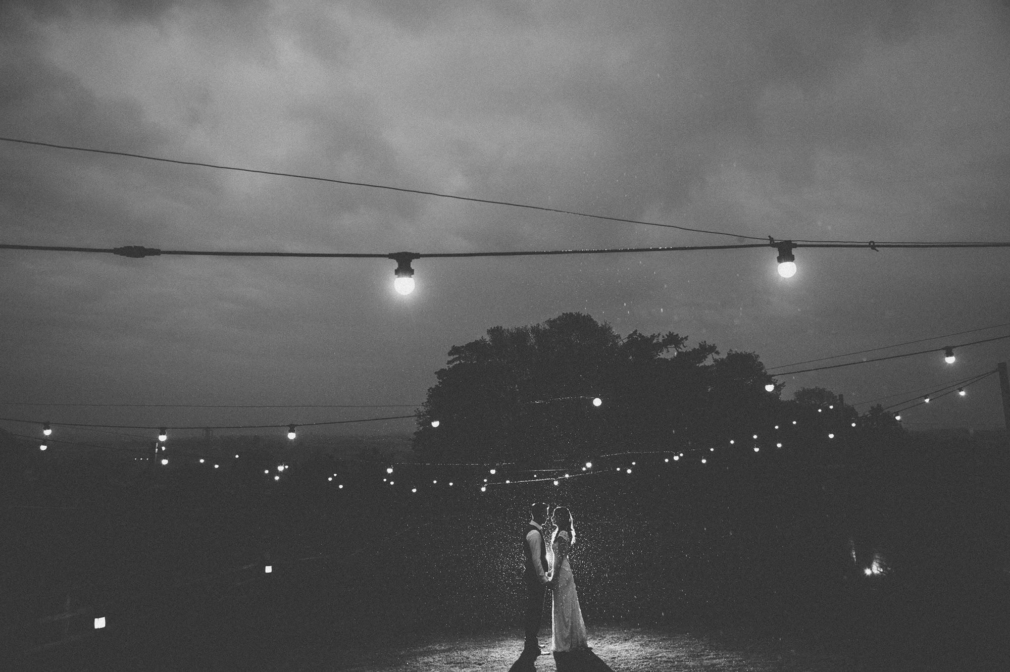 Bride and Groom stand undr festoon lights in the rain at night at Upton Barn wedding venue