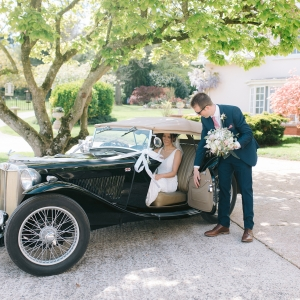 Bride arrives in vintage car and is helped out by groomsmen