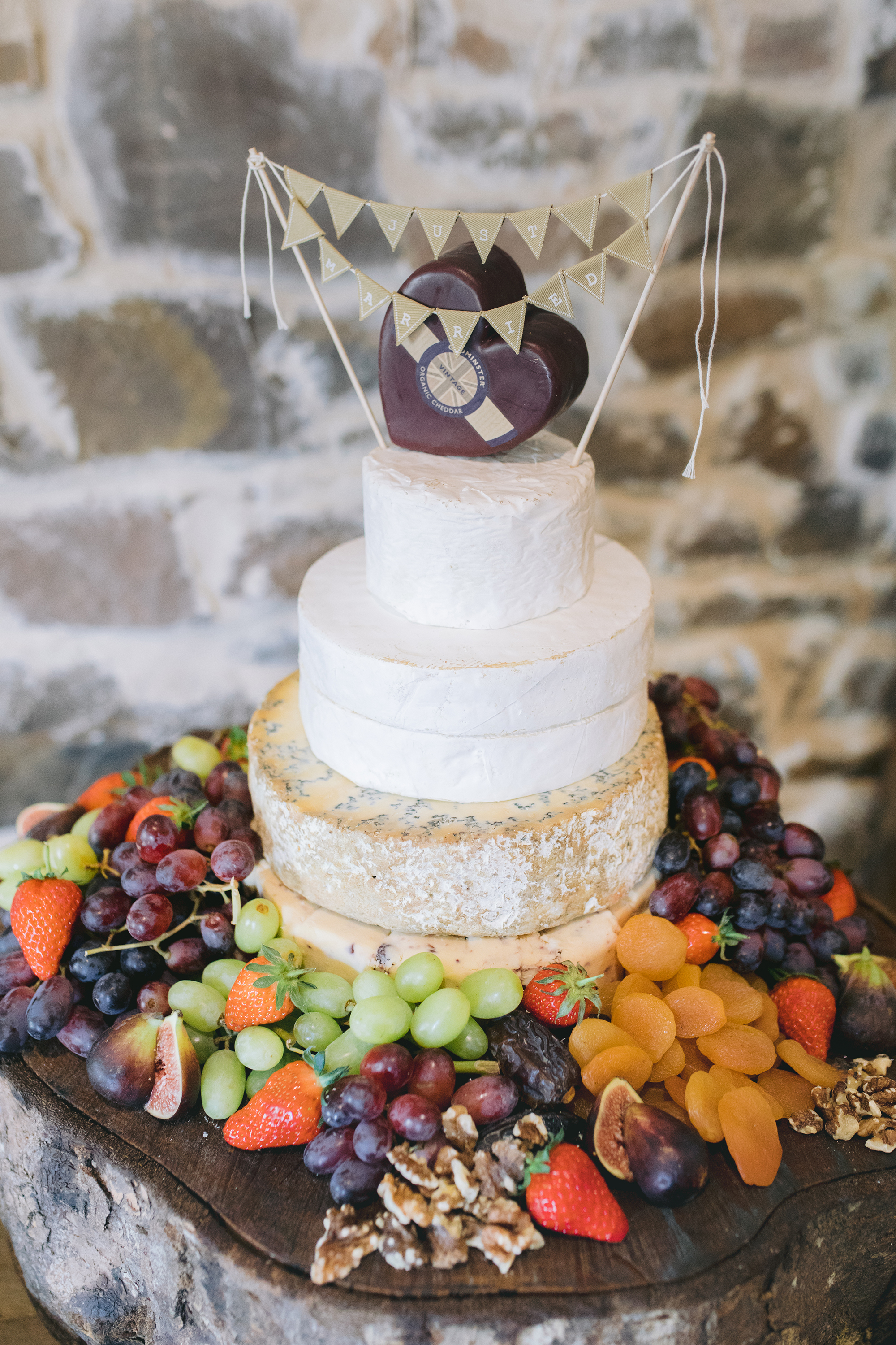 Wedding Cake of Cheese with Just Married mini bunting displayed on a wooden tree trunck slice