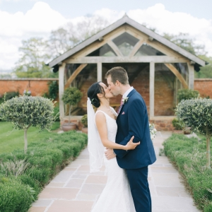 Bride and Groom kiss in front of the Arbour at Upton Barn and Walled Garden