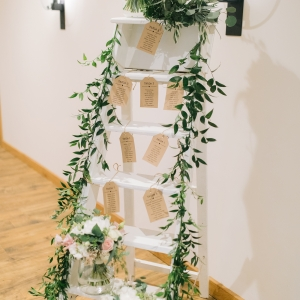 White step ladder with table plan for guest in the The Stable Barn