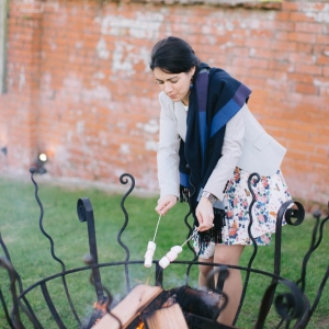 Guest toasts marshmellow skewers over a fire pit at Upton Barn and Walled Garden