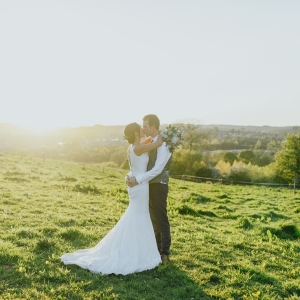 Bride and Groom embrace and kiss infront of rolling Devon countryside views