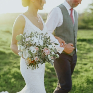 Close up of Bride and Groom walking ar in arm with her bouquet in the foreground