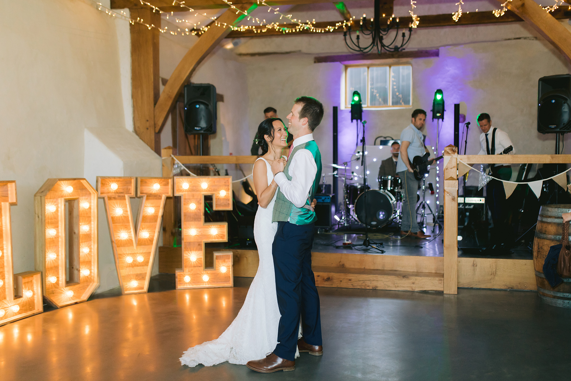 Bride and Groom perform their first dance in front of giant light up Love letters and a live bandand