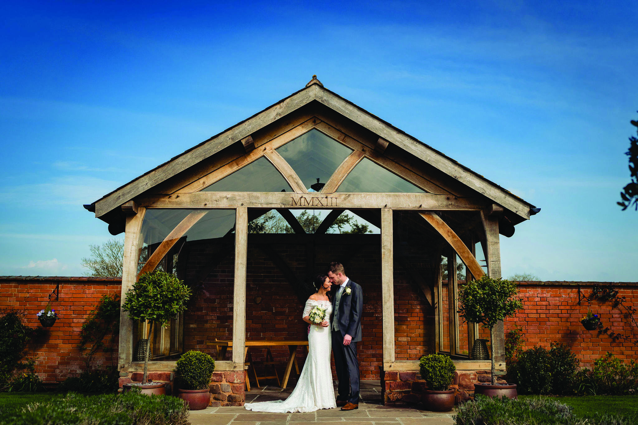 Bride and Groom embrace in the Arbour at Upton Barn