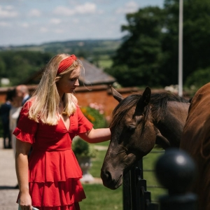 Wedding guest pets a horse at the entrance to Upton Barn
