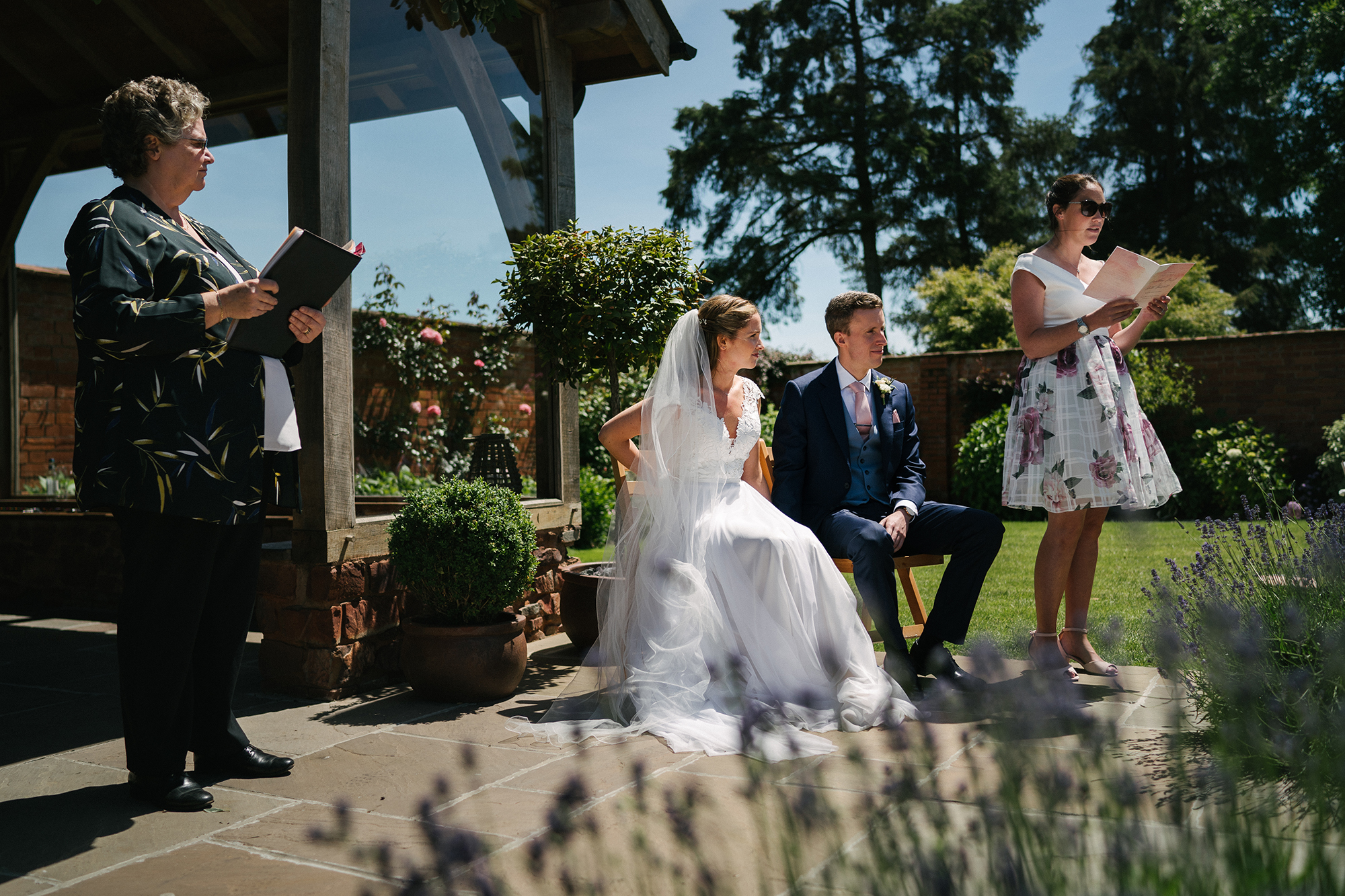 Guest gives a reading for the Bride and Groom by the arbour in the Walled Garden at Upton Barn while they and the Registrar look on.