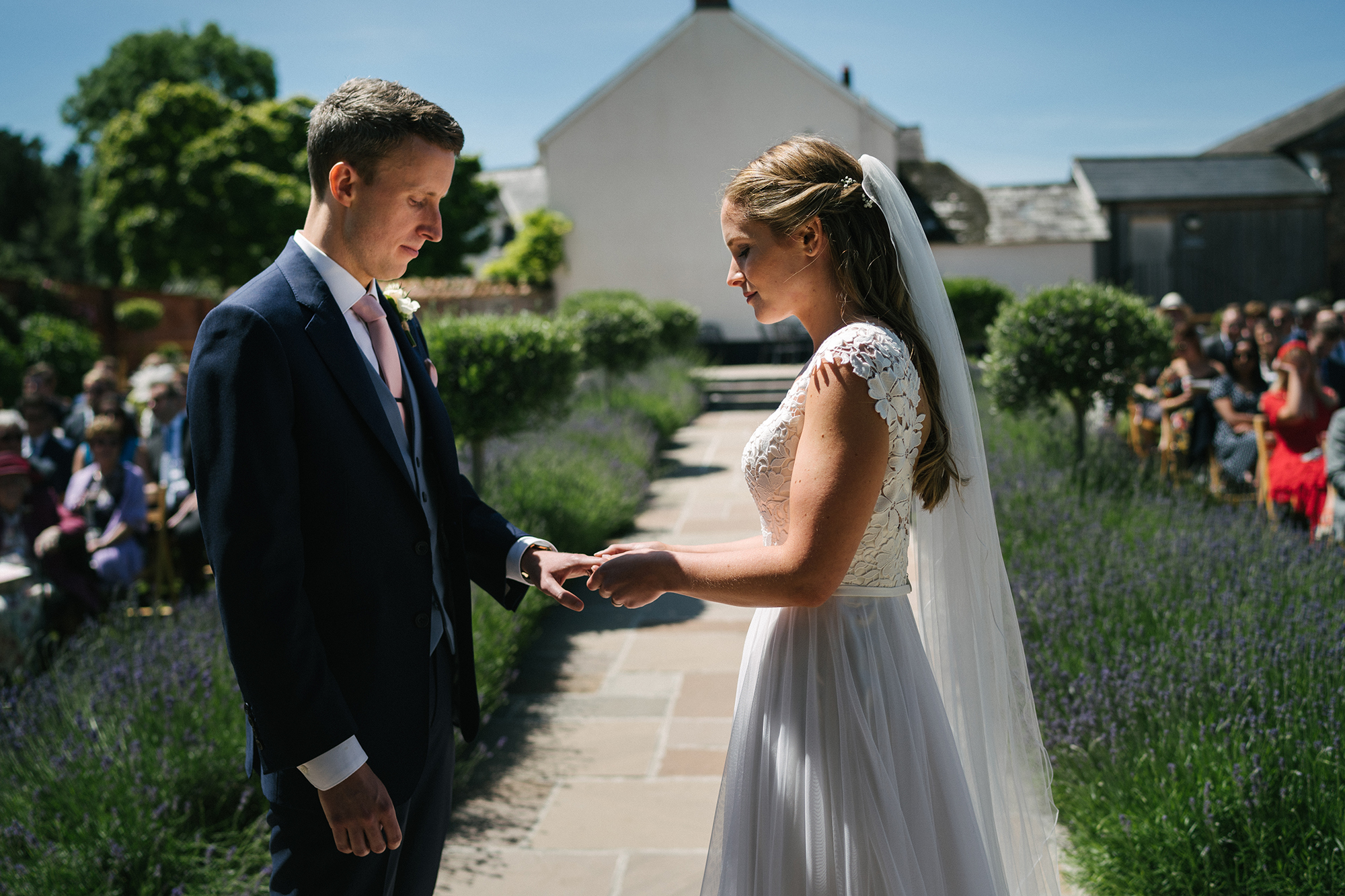 Bride places the ring on her grooms fingers in front of guests in Walled Garden