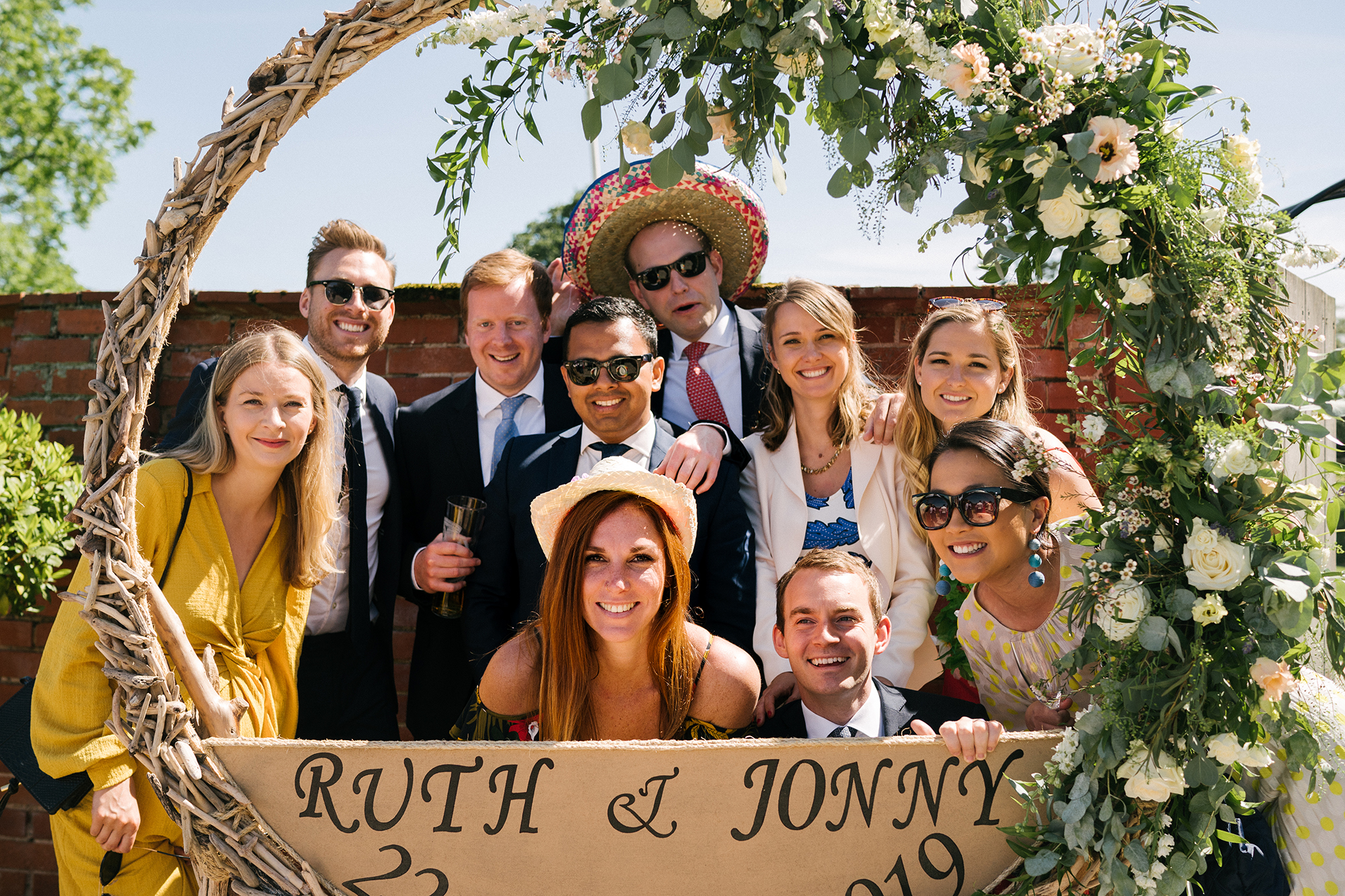 Fun wedding guest join in for a group photobooth photo in a round frame in the Walled Garden