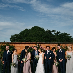 Bride, Groom, Bridesmaids and Grooms men join for a long line casual photo in the Walled Garden at Upton Barn