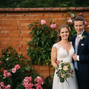 Bride and Groom smile and embrace infront of rose covered wall in the Walled Garden at Upton Barn
